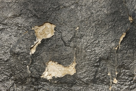 hydrophobic: Fragment of old wall with a shelled hydrophobic coating of black pitch