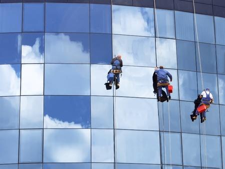 blue facades sky: Workers of steeplejack washing a skyscraper windows