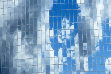 Blue sky with clouds reflected in glass windows of skyscrapers in the big mirror as photo