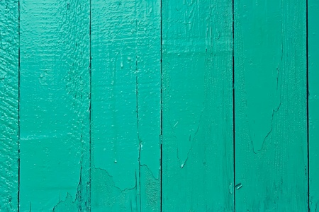 Fragment of old wooden fence painted in bright aquamarine