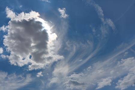 Beautiful cloudscape. Sun behind the cloud, warm summer day photo
