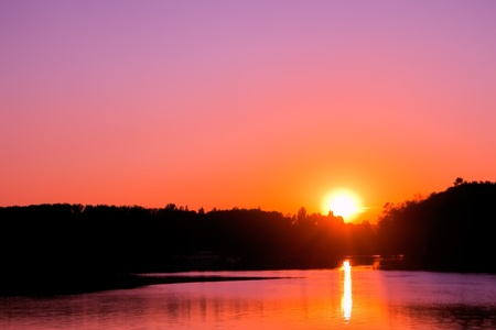 the setting sun: Sunset over lake. Setting sun on the cloudless sky