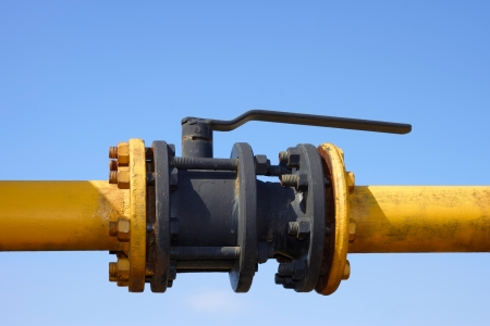 The gas valve on the background of clear blue sky. Blocking damper on gas pipe Stock Photo