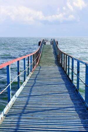 remoteness: Old wooden sea pier that goes away Stock Photo