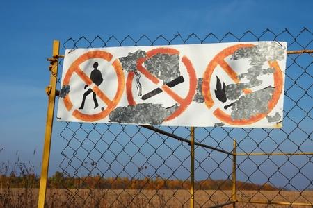 tachado: Mesa de edad con signos prohibitivos y pintura c�scara colgando en las cercas de malla en los campos