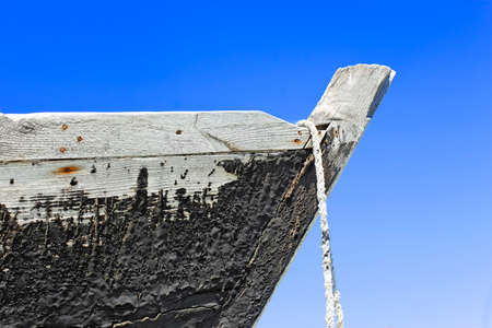 prow: The prow of the old wooden boat with a tarred surface against blue sky Stock Photo