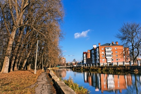 City house above the river canal near the old park. Late autumn urban landscape photo