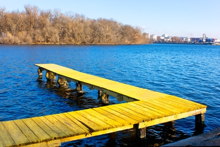 Old wooden pier at the city water reservoir in a fine late autumn day photo