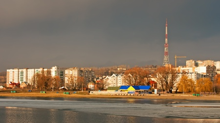 looming: City buildings over the river in bright sunlight, on the other side a dark cloud looming over the city. Khmelnytsky, Ukraine