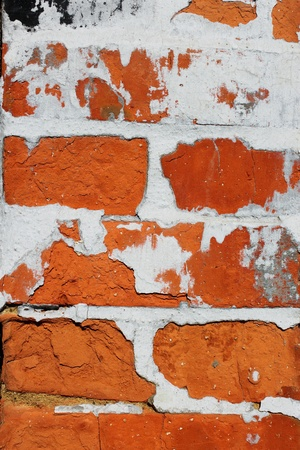 Fragment of old brick wall with concrete covering shelled close up photo