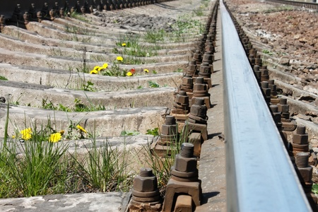 Railway rail in spring season close-up. Dandelions flowering between railroad ties among gravel photo