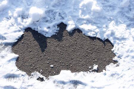 snowbanks: Fragment of the asphalt surface between snowbanks Stock Photo