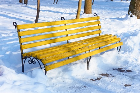 Yellow wooden bench among the snowbanks in winter park on a sunny fine day  photo