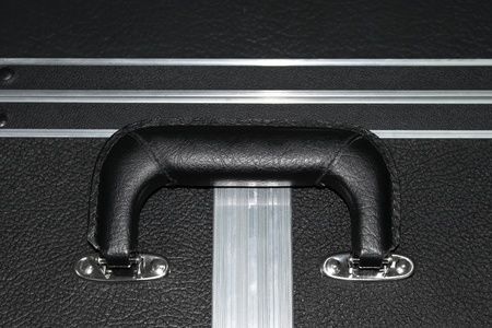 rigidity: Fragment of a large suitcase with black artificial leather with a handle and aluminium edges of rigidity