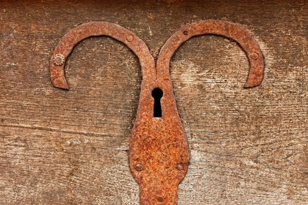 Fragment of ancient outmoded wooden chest with rusty metal plate and hole for key Stock Photo - 13107445