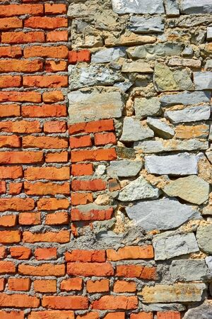 Wall partially from formless stone and red brick photo