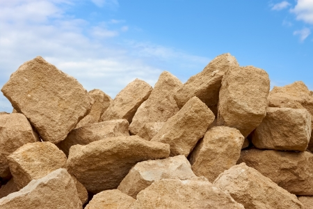 Heap of large shapeless blocks of limestone against the background of blue sky