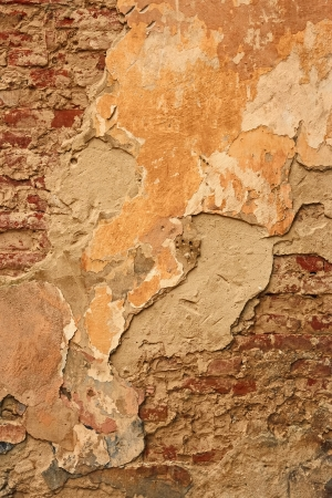 Fragment of old brick wall with ragged plaster and multiple whitewash layers photo