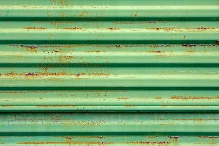 Old rusty metal ribbed surface painted in green color photo