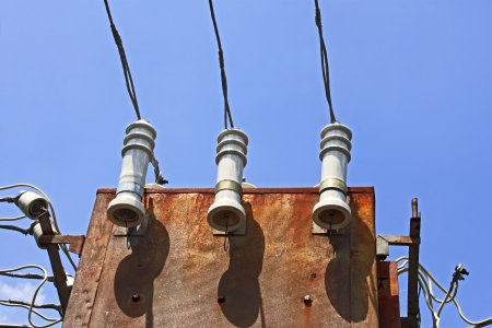 insulators: Electric insulators and wires on the old three-phase electrical transformer on a background of blue sky Stock Photo