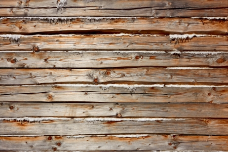 Old wooden logs with heat insulation material between them. Part of wooden house walls photo