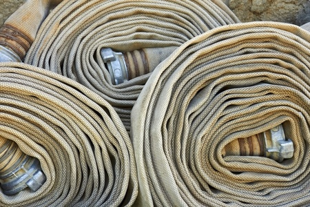 Old rolled fire hoses with nozzles close-up photo