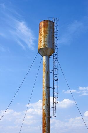 Large old metal water tower on the background of blue sky photo