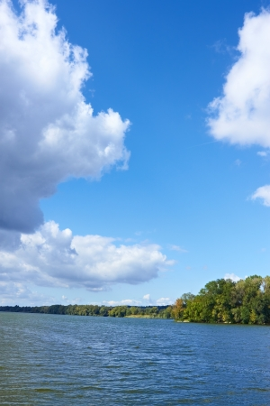 Beautiful cloudy scenery over the river in early autumn. Vertical photo