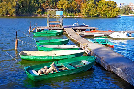 Group of small fishing boats and other craft are tied near the old pier Southern Bug River in Khmelnytsky, Ukraine