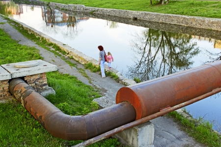 effluent: Woman and little girl going by waters bank. Large rusty metal pipe over the reservoir. View from the top Stock Photo