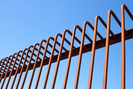 Detail of fence with bent metal rods against a blue sky photo
