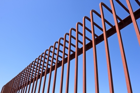 Fragment of fence with bent metal rods against a blue sky photo