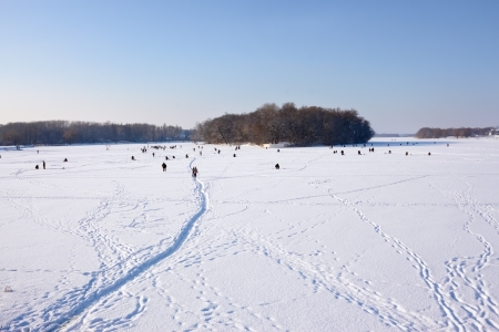 Winter scene. Fishermans catch fish in river on the ice surface with snow
