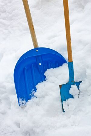 Plastic and metallic blue shovels with wooden handles in the snow heap Stock Photo - 17997440