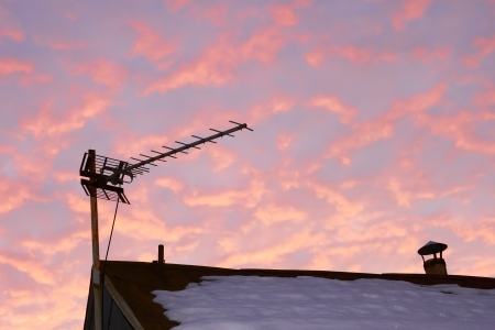 Television antenna over the snowy roof of the old house against reddish cloudy sky in evening time
