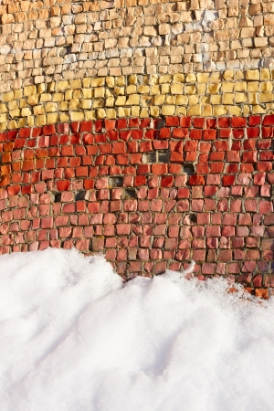 zoned: Fragment of an old colortul mosaics partially covered with snow in fine winter day