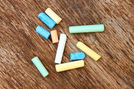 cylindrical: Diversi pezzi cilindrici di gesso colorato sulla vecchia eroso bordo marrone Archivio Fotografico