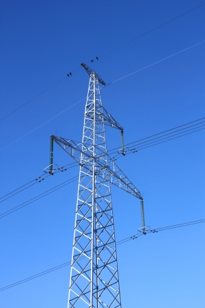 Electrical high-voltage metal pillar against the background of blue cloudless sky photo