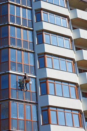 installer: Installer worker makes the finishing on the facade with windows of a new modern skyscraper