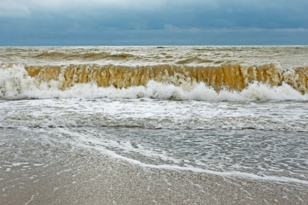 ashore: Big stormy wave with sand contaminated water directed ashore