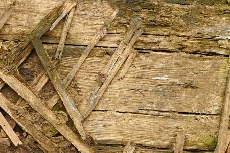 Detail of an old dilapidated wooden walls. Wooden slats are used as fitting with mud photo