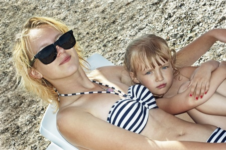 Different years two Caucasian sister girls resting on the beach photo