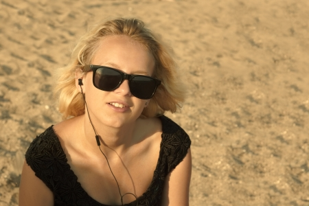 Beautiful young blond girl with glasses and headphones on the background of a sandy beach, edited with sepia photo