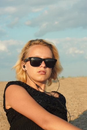 Beautiful teenage blond girl with glasses and headphones on the background of a sandy beach and cloudy sky photo