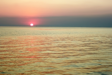 Red sun in the clouds near the horizon over the sea bay photo