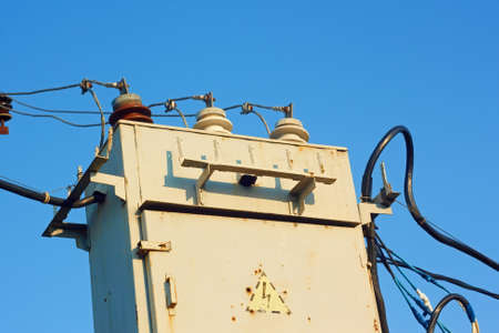 Old transformer with insulators and wires on a background azure sky photo