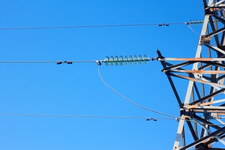 insulators: Insulators, wires, and fragment of metal electrical tower on the background of blue sky Stock Photo