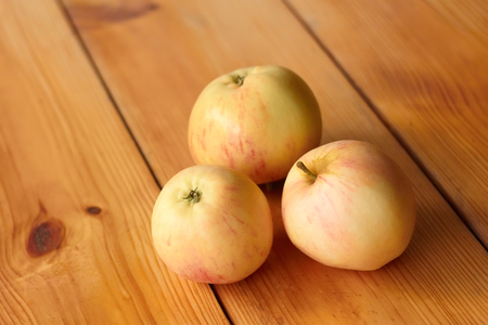 Three ripe apples on a lacquered wooden table photo