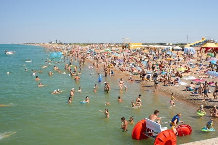 saki: NOVOFEDORIVKA, CRIMEA, UKRAINE � JULY 07, 2013: Many people relaxing on the beach on July 7, 2013 in Novofedorivka, Crimea, Ukraine. Novofedorivka a resort that is developing rapidly in recent years. It is a resort about 5 kilometers from Saki mud resort