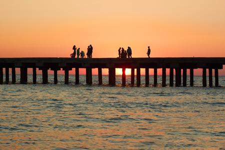 bewonderen: Groepen van mensen die op de oude pier genieten van de prachtige zonsondergang over de Zwarte Zee kust in de Krim, Oekraïne Stockfoto